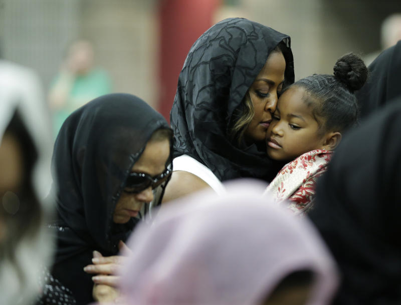 Muhammad Ali's wife Lonnie and her daughter Laila attend Muhammad Ali's Jenazah, a traditional Islamic Muslim service, in Freedom Hall, Thursday, June 9, 2016, in Louisville, Ky. Laila is holding her daughter Sydney Jurldine Conway. (AP Photo/David Goldman)